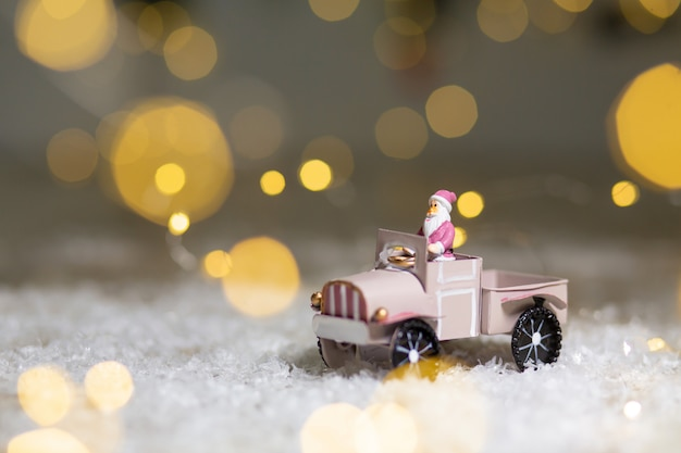 クリスマステーマの装飾的な置物。サンタの像は、ギフト用のトレーラーを備えたおもちゃの車に乗る。