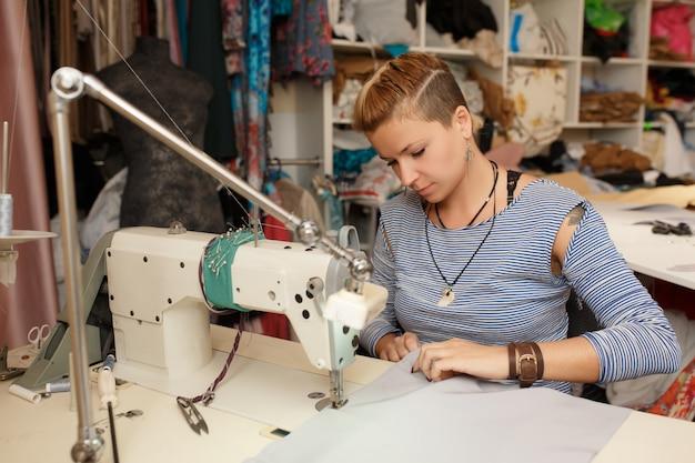若い女性の金髪洋裁布デザイナーはミシンで動作します。彼女のワークスペースで。