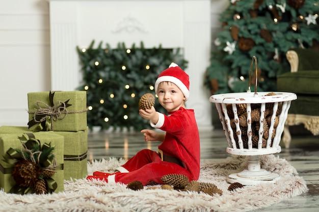 クリスマスツリーを飾るためにコーンで床で遊ぶかわいい幼児の肖像画。クリスマスツリーとクリスマスプレゼントの箱の近く。メリークリスマスとハッピーホリデー