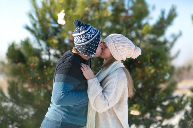冬の森の中でお祝いおもちゃや花輪で飾られた緑のクリスマスツリーの女の子のキスを持つ男。冬のロマンス