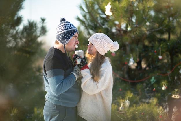 女の子と男は、温かい飲み物のマグカップと冬の森で歩くとキスします。温かい飲み物を飲みながら森の中を心地よい冬の散歩。愛情のあるカップル、冬休み