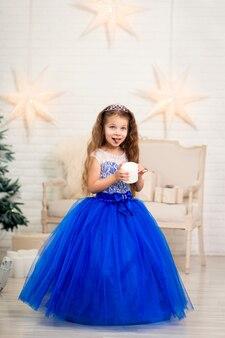 Милая маленькая девочка в великолепном синем платье держит в руках искусственную свечу для украшения дома
