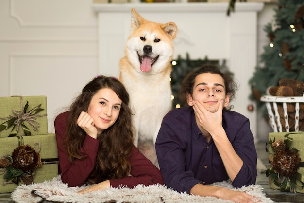 自宅でクリスマス休暇のための床に愛らしい秋田犬犬を抱きしめる若い幸せなカップル。