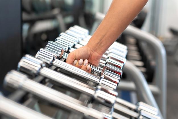 Женская рука принимает гантели формы рядов гантелей в тренажерном зале
