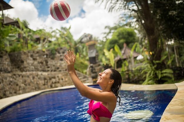 ピンクの水着の若いセクシーな女性は、熱帯のスイミングプールでボールで遊ぶ。