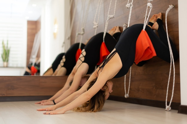 女性がジムでストレッチロープでヨガを練習します。フィット感と健康
