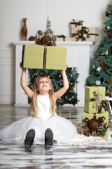 彼女の頭の上に贈り物の大きな箱を持って幸せな女の子。冬の休日、クリスマス、人々の概念