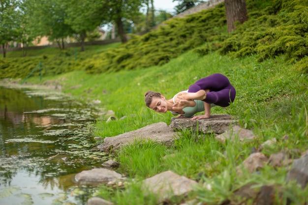 Худенькая брюнетка занимается спортом и выполняет красивые и сложные позы йоги в летнем парке. зеленый пышный лес и река на заднем плане. женщина делает упражнения на коврик для йоги