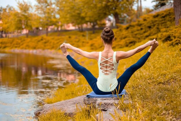 Стройная молодая брюнетка-йога выполняет сложные упражнения йоги на зеленой траве осенью на фоне природы