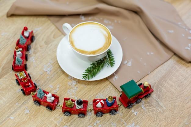 Вкусный свежий праздничный утренний кофе капучино в керамической белой чашке на деревянном столе с декоративным рождественским шлейфом, красными орнаментами, светлячками и еловыми ветками
