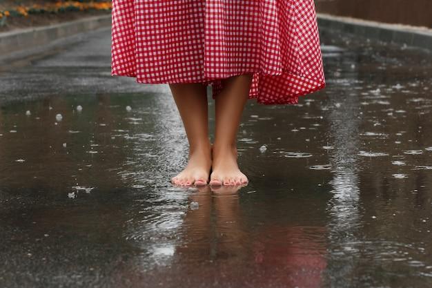 夏の雨の後、水たまりで踊る少女の足のクローズアップ。