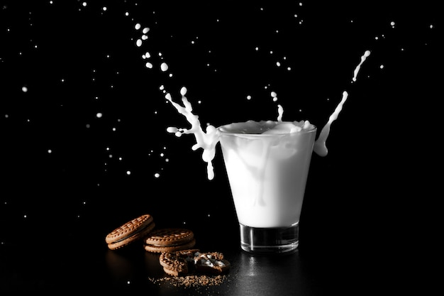 黒の背景にミルクとチョコレートクッキーのガラスのスパルシュ