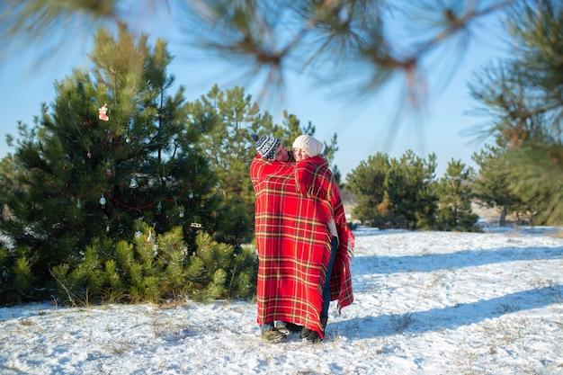 冬の森を歩く男は、彼女を暖めるために、暖かい赤の格子縞の格子縞で彼のガールフレンドを包みます