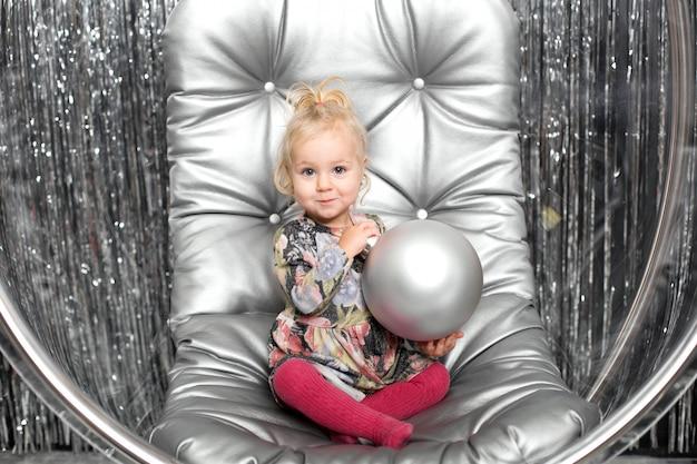 Маленькая девочка играет в кресле стеклянный шар с серебряными шариками. снежная королева