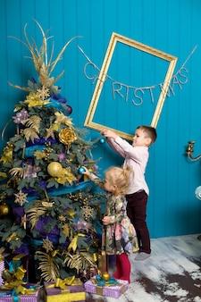 Милая маленькая девочка и мальчик украшают елку. брат и сестра в канун рождества