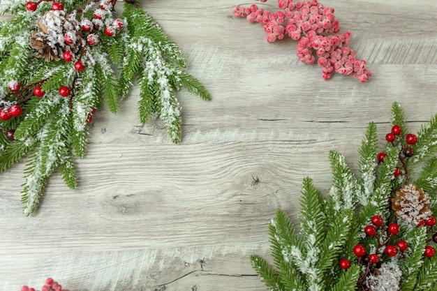 Рождественские украшения. еловая ветка с красными ягодами лежит на светлом деревянном фоне