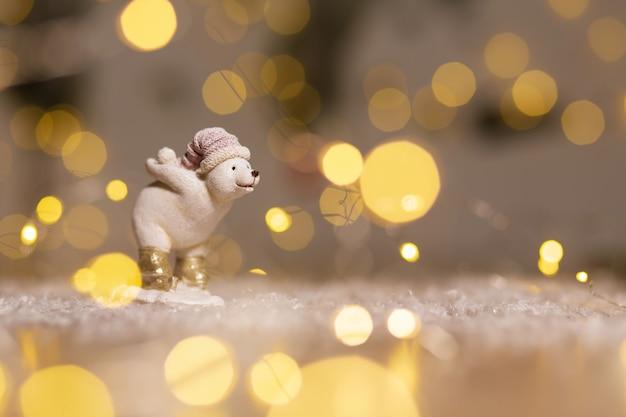 Декоративные статуэтки на рождественские темы. статуэтка белого медвежонка держит снежный ком сзади. елочные украшения. праздничный декор, теплые огни боке.
