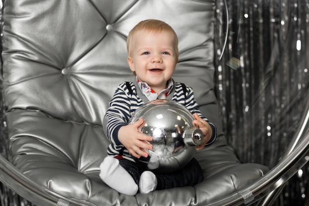 Маленький мальчик играет в кресле стеклянная чаша с серебряными шариками.