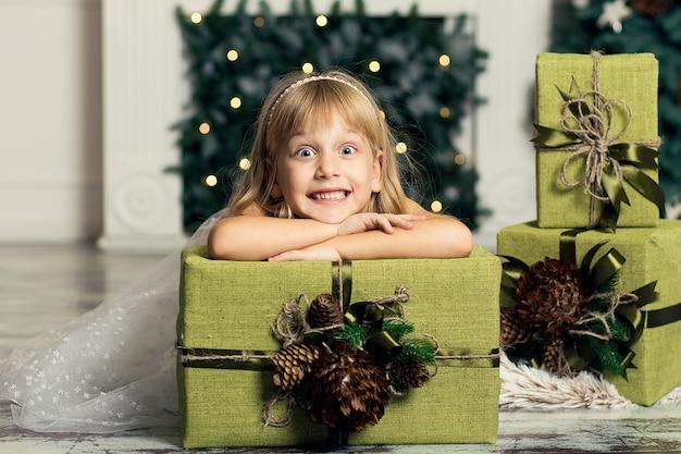 Счастливая девушка держит большую коробку с подарком над ее головой.