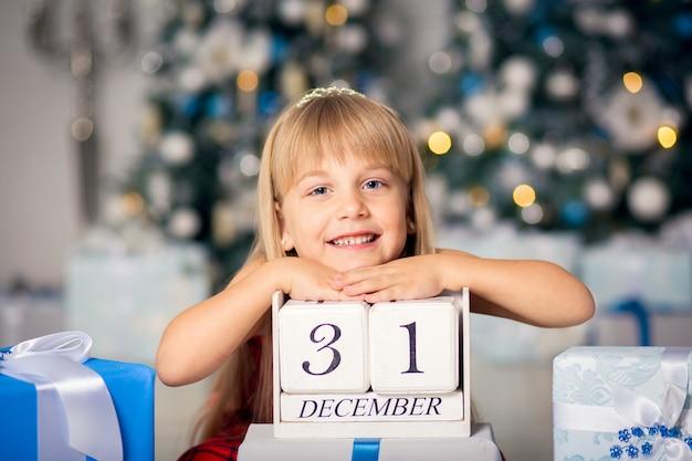 Счастливая маленькая усмехаясь девушка с подарочной коробкой рождества.