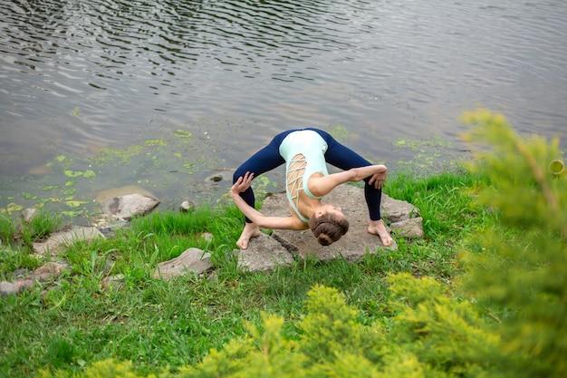 Стройная брюнетка занимается йогой летом на зеленой лужайке у озера