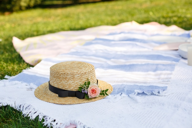 新鮮な花と麦わら帽子は、緑の芝生の明るい夏の日に白いピクニック毛布の上に横たわっていた