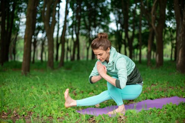 Худенькая брюнетка занимается спортом и выполняет красивые и сложные позы йоги в летнем парке.