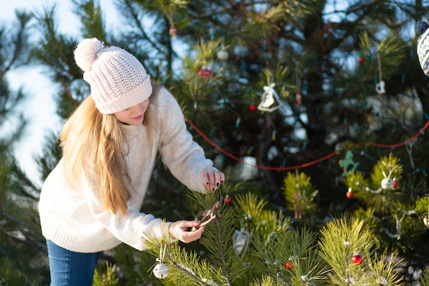 女の子は装飾的なおもちゃで飾って、森の冬の路上で緑の木を花輪します。