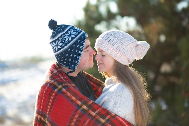 冬は森の中を歩きます。赤い格子縞の格子縞に包まれた少女と男
