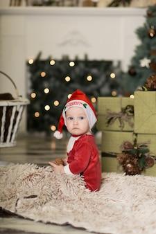 クリスマスツリーを飾るためにコーンで床で遊ぶかわいい幼児の肖像画。