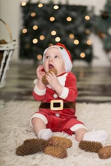 Портрет милый малыш играет на полу с шишками, чтобы украсить елку.
