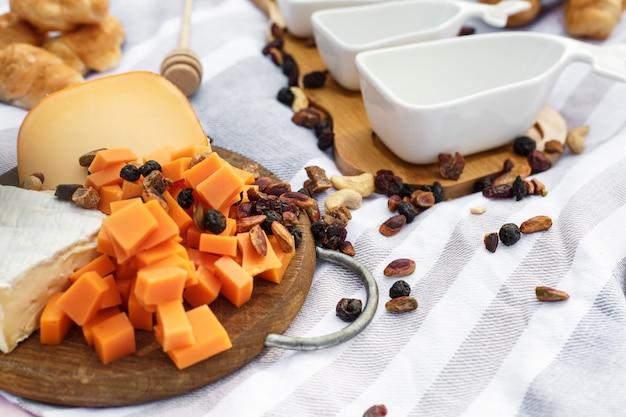 青いピクニック毛布にチーズ盛り合わせレイアウトの木製トレイ