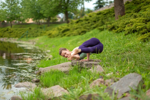 若いスポーツ少女は、川沿いの緑の芝生でヨガを練習します。