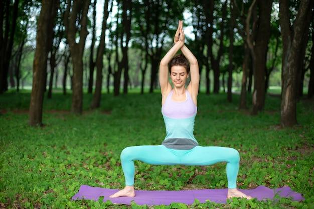 Молодая спортивная девушка занимается йогой в тихом зеленом лесу летом, в позе йоги.