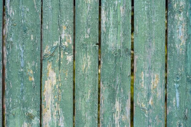 Старый деревянный забор светло-зеленая краска пилинг текстуры доски. задний план