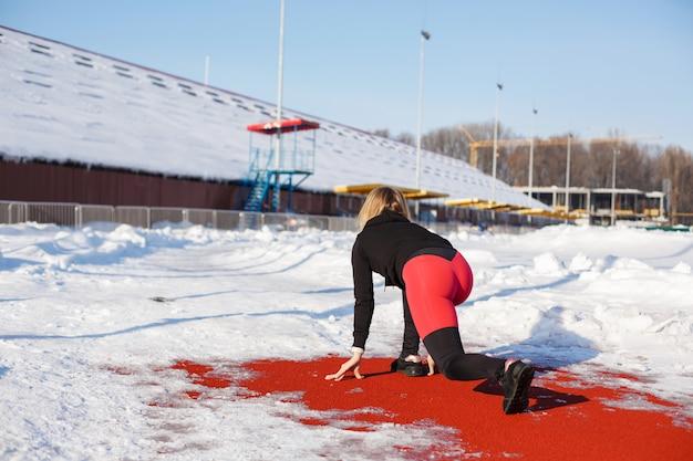 Девушка в спортивной одежде на дорожке для бега по заснеженному стадиону готовится к пробежке.
