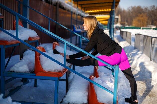 Молодая кавказская женская блондинка в фиолетовых гетры протягивая тренировку на трибуне на снежном стадионе.