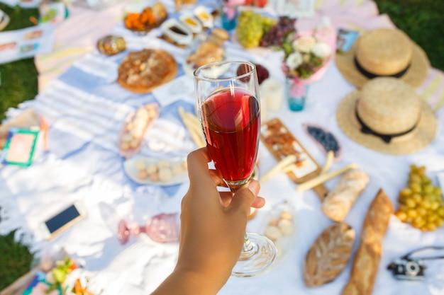女性はピクニックで赤いシャンパンとワイングラスを保持します。