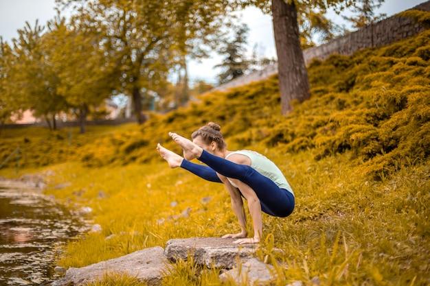 スリムなブルネットの少女はスポーツに行き、湖のほとりで自然の中でヨガのポーズを実行します