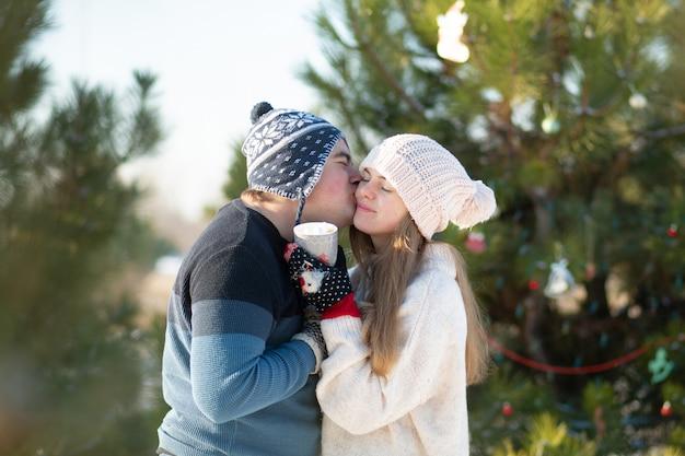 女の子と男は、温かい飲み物のマグカップと冬の森で歩くとキスします。