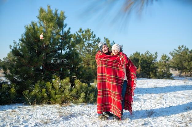 森の中で冬を歩く男は、彼女を暖めるために、彼のガールフレンドを暖かい赤の格子縞の格子縞で包みます