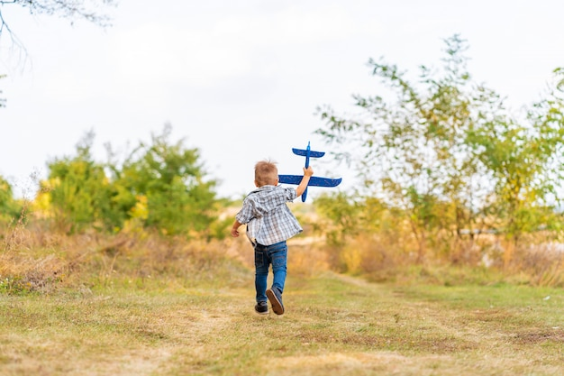 若い男の子は手でおもちゃの飛行機と遊ぶ。