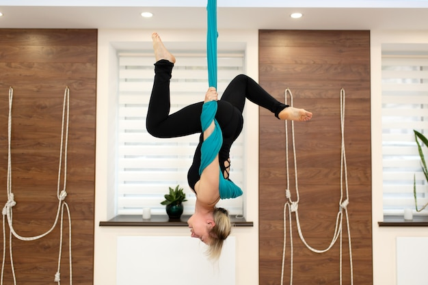 ハンモックで逆さまにぶら下がっている女性。ジムでヨガのクラスを飛ぶ。フィットと健康のライフスタイル