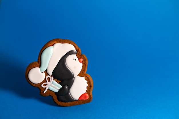 Пряничное печенье милого пингвина с подарком на синем