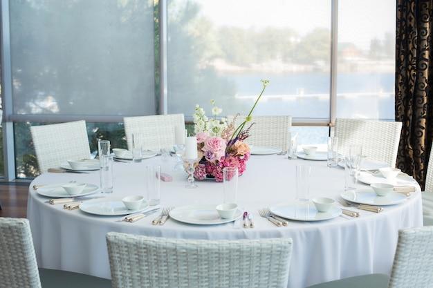 イベントの白いレストランのテーブルを提供し、ゲストを待ちます