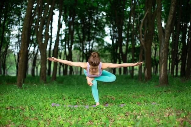 若いスポーツ少女は、やめられた緑の夏の森、ヨガのアサンの姿勢でヨガを練習します。