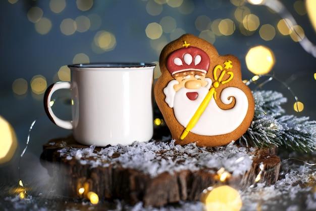 Праздничная традиционная пищевая пекарня, пряничный добрый волшебник в уютном убранстве с гирляндами и чашкой горячего кофе