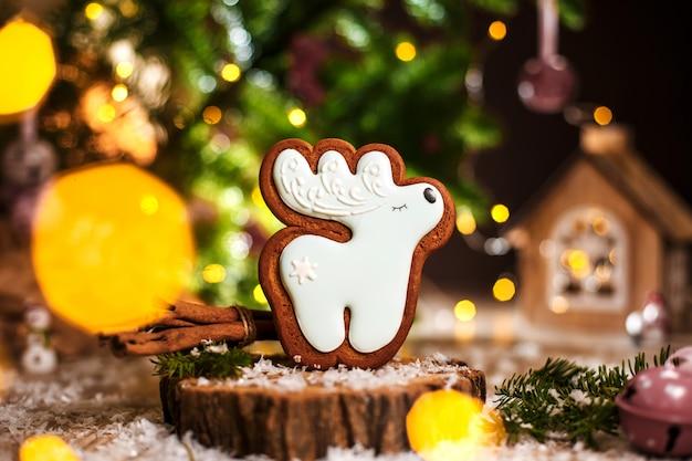 Праздничная традиционная еда, пекарня, пряничный белый рождественский олень в уютном теплом убранстве с гирляндой