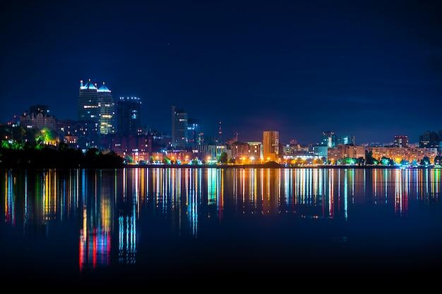 多くの色の光が水に反映されている都市の遊歩道の夜の風景