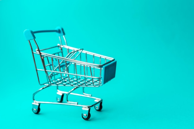 緑、割引、ショッピングコンセプトに空の金属ショッピングトロリー